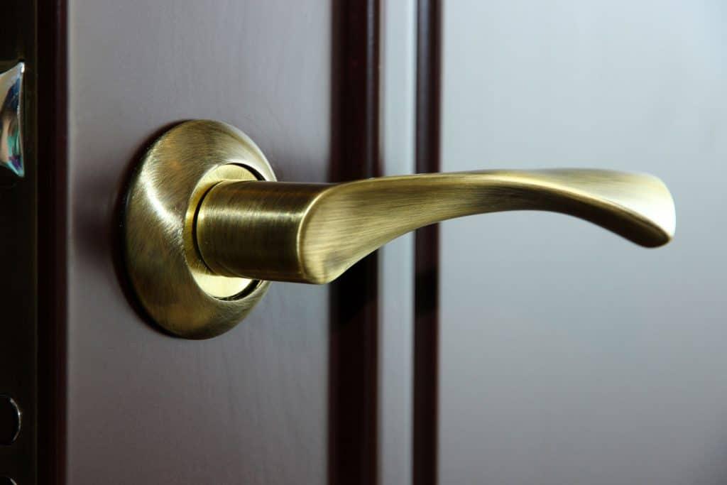A brass polished door handle installed in a hand wood door
