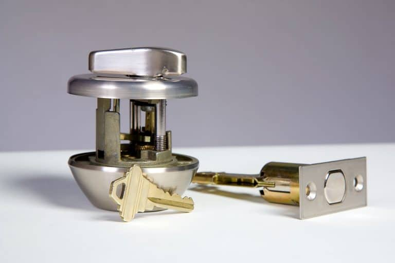 A deadbolt lock and key laying on a white table, What Is The Standard Size Of A Deadbolt?