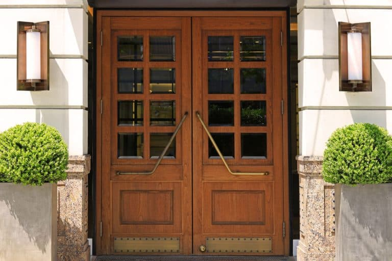 A wooden French door with small shrubs on the side, Should You Prime Fiberglass Door Before Painting?