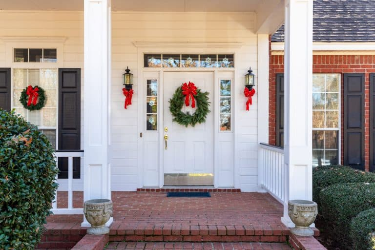 A fiberglass door with a white painted door with a green Christmas wreath, How To Hang A Wreath On A Fiberglass Door