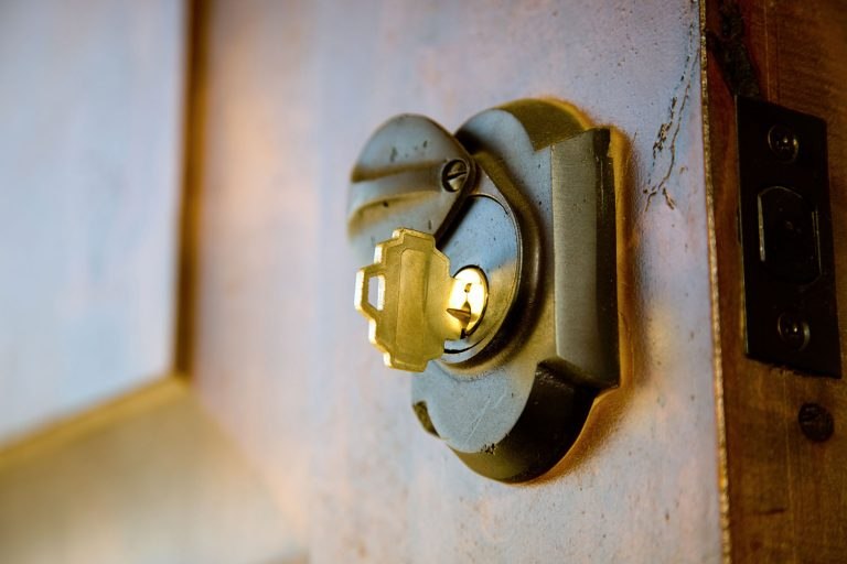 A golden key inserted on the deadbolt lock of a front door, How Much Does A Deadbolt Cost?