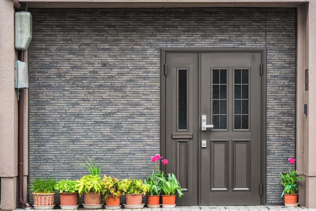 A gorgeous gray themed front porch decorated with flowers in front, Do Doors Come With Holes For Handles?