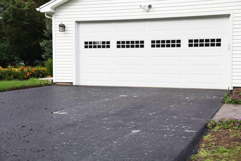 A huge white garage door with an asphalt driveway, Are Garage Doors Universal?