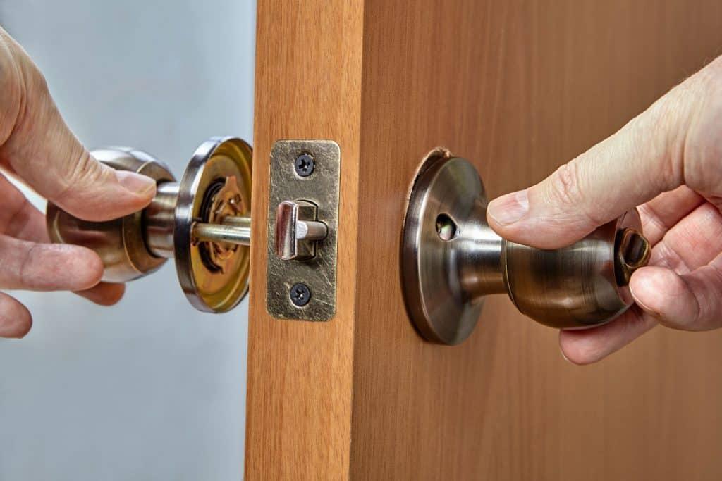 A man installing a door knob on the wooden door