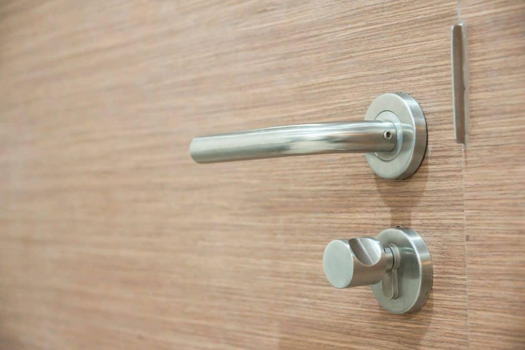A stainless steel door handle installed in a wooden front door