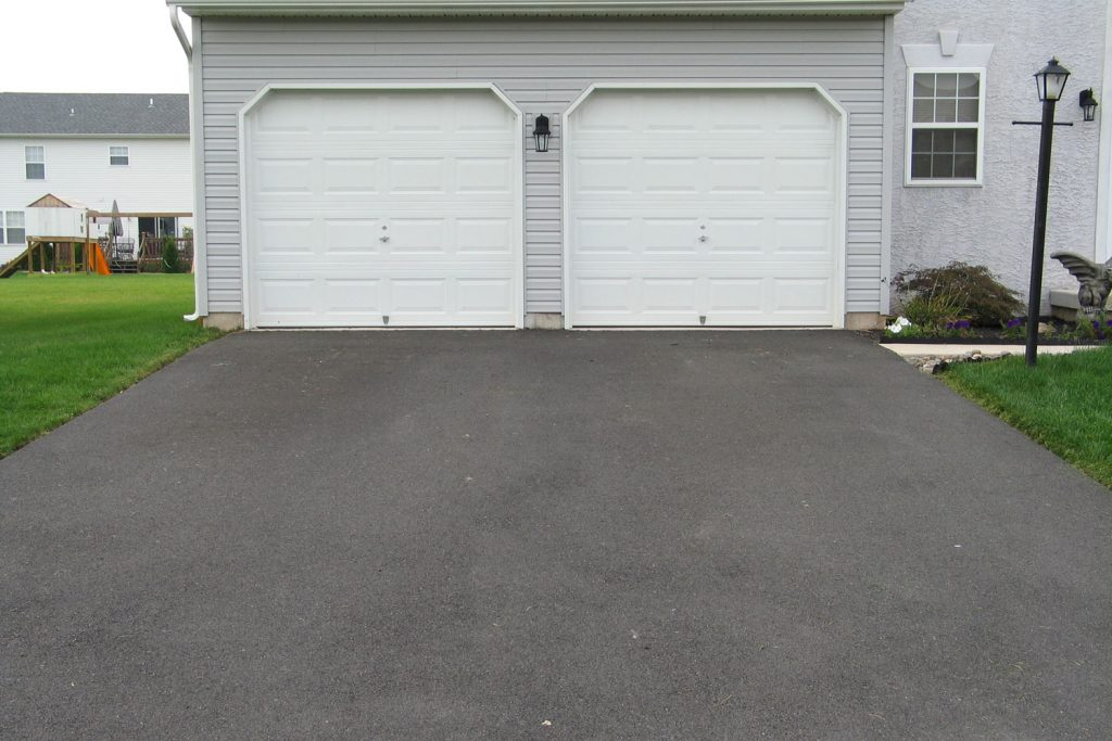 A two way garage door painted in white and an asphalt driveway