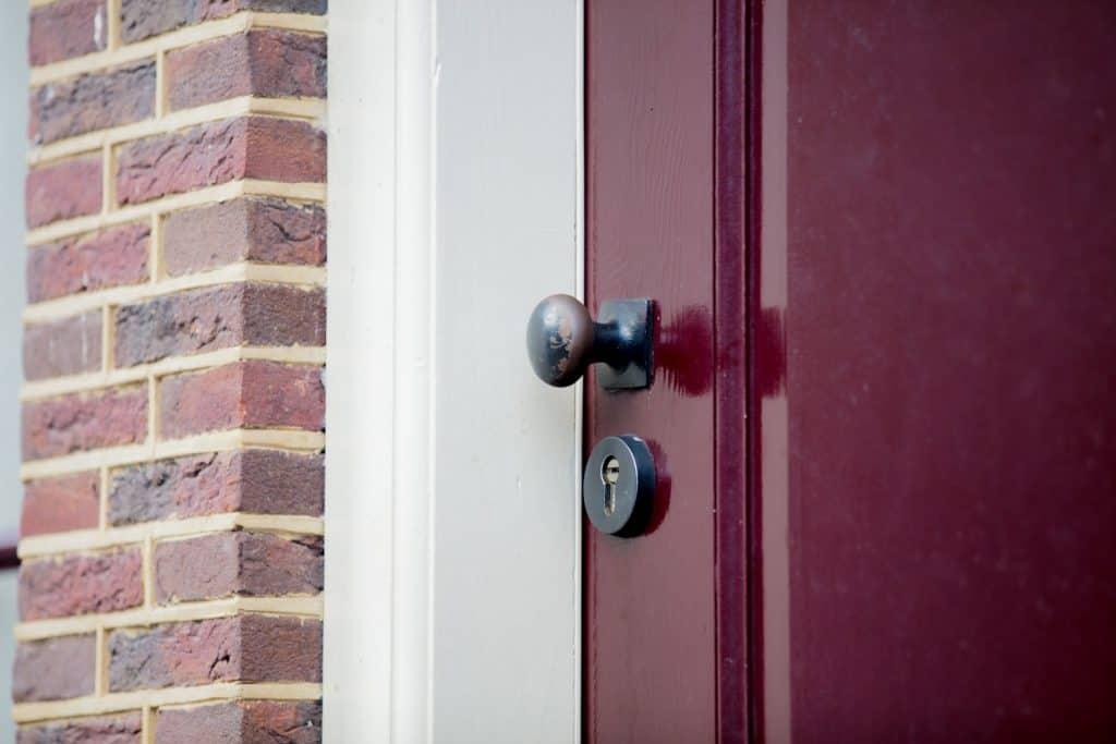 A violet colored front door with a black colored door knob