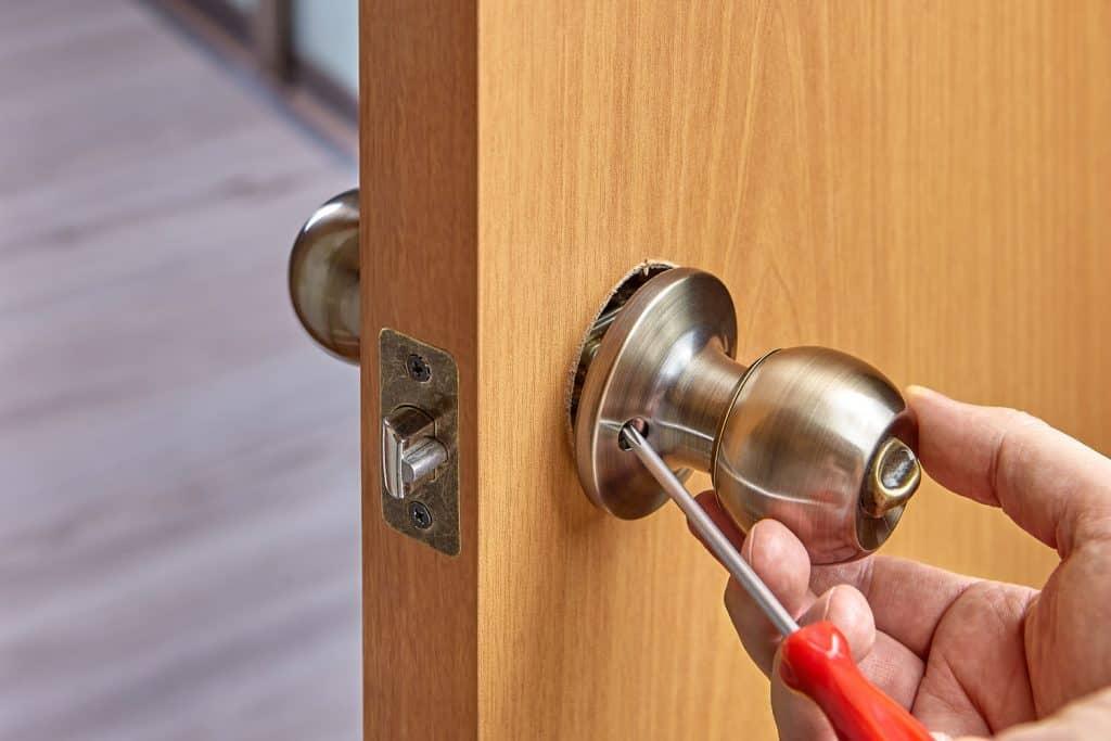 A worker screwing a door knob on the door