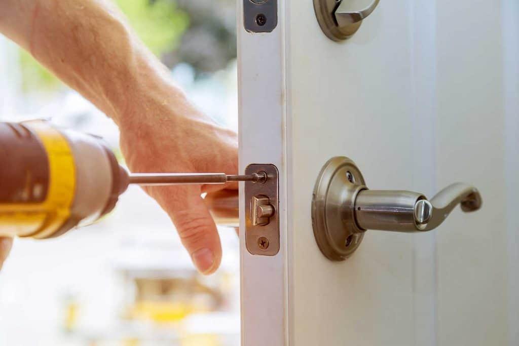 Close up of a worker installing deadbolt lock on door