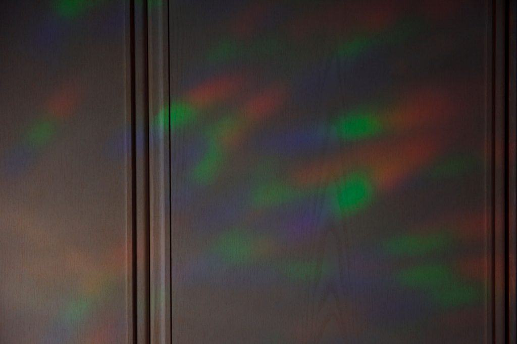 Colorful light in the early morning reflected in the white wooden fiberglass door