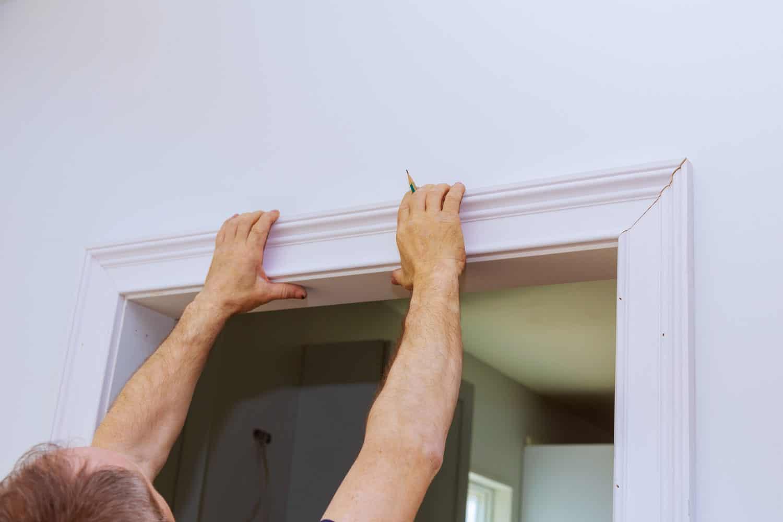 Construction handyman installing the interior door molding