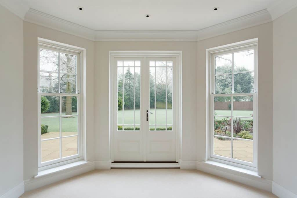 Interior of a white painted living room with a fiberglass double door