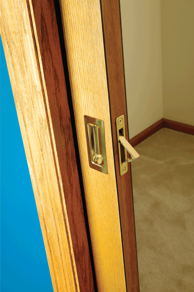 Open wooden pocket door slid back into the wall cavity concealing it and saving space with close up focus to the handle and pull edge lever