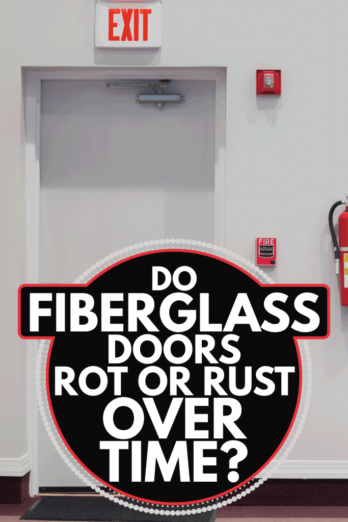 Vertical shot of an emergency exit door with a fire alarm, fire extinguisher, and an emergency light hanging on the wall next to it. Do Fiberglass Doors Rot Or Rust Over Time