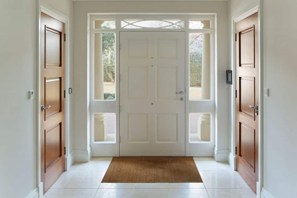 Interior of a grand foyer painted in white with two wooden doors leading to different room