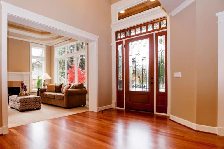 Interior of a rustic contemporary house with wooden flooring, a wooden fiberglass door, and a beige painted wall, How Long Does It Take For Gel Stain To Dry On Fiberglass Door?