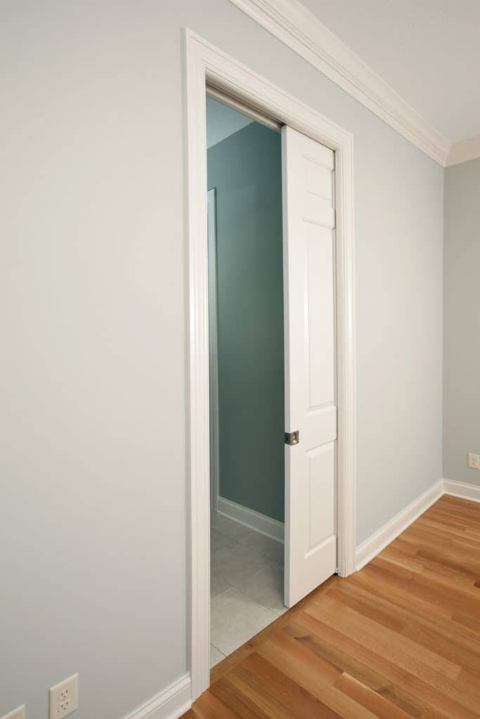 A pocket door inside a white painted living room with wooden laminated flooring