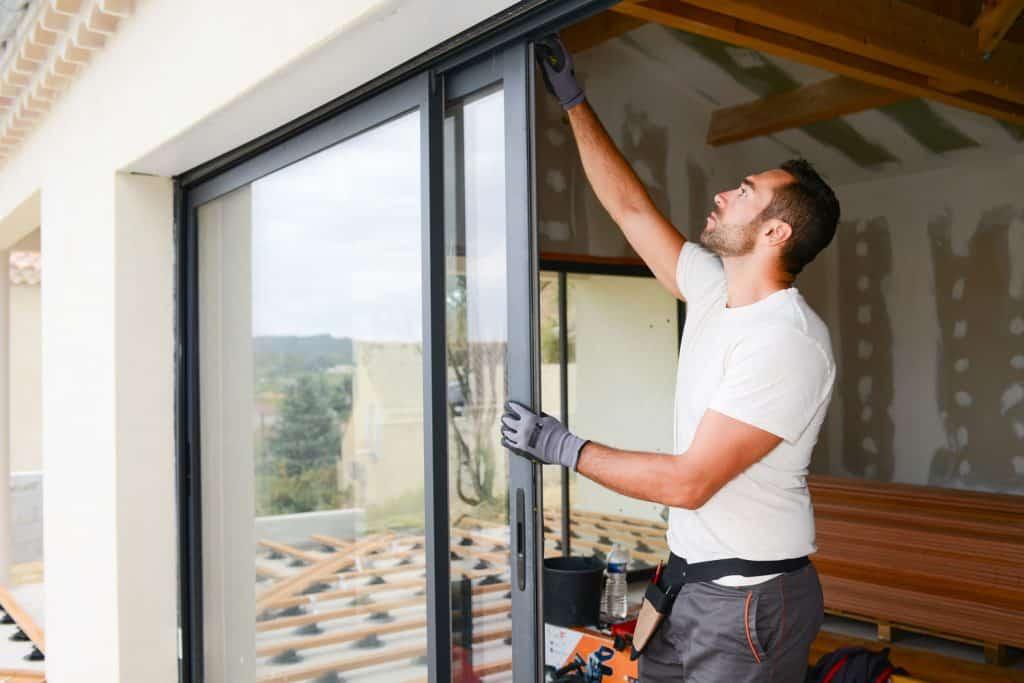 A repair man placing a bolt on the sliding door