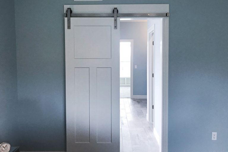 A white painted barn door inside a light blue painted bedroom wall, Can A Barn Door Be Hung From The Ceiling?
