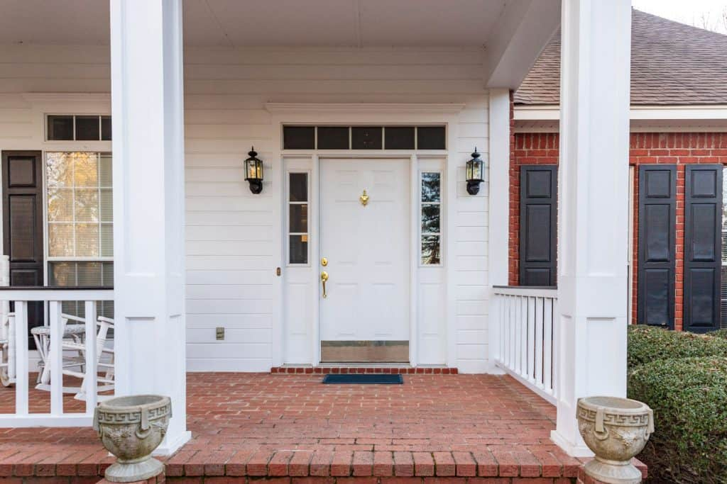 A white painted porch with glass window panes and a glass header