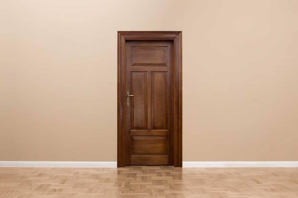 An empty room with brown wooden door