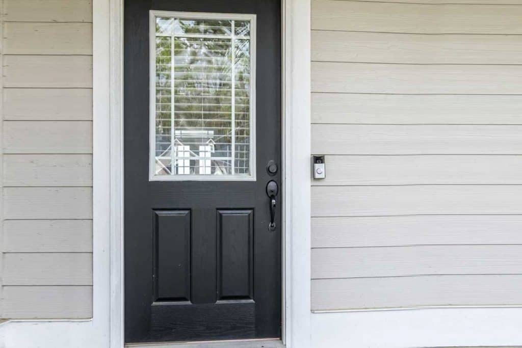 Black front door of a tan beige new construction house with siding