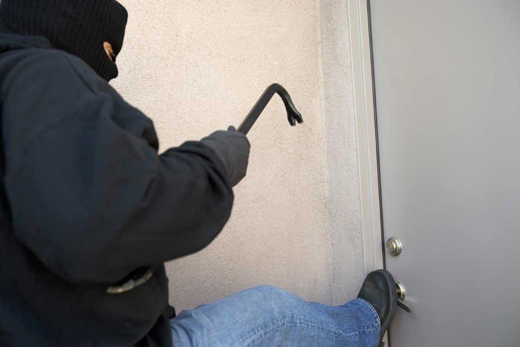 Burglar kicking door of a house