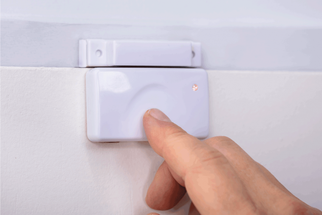 Close-up Of A Person's Finger Pressing Security System Door Sensor. How To Stop Alarm From Beeping When Door Opens