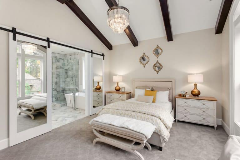 Interior of a white modern bedroom with carpeted flooring and a sliding glass on the side, Do Glass Doors Block Wi-Fi?