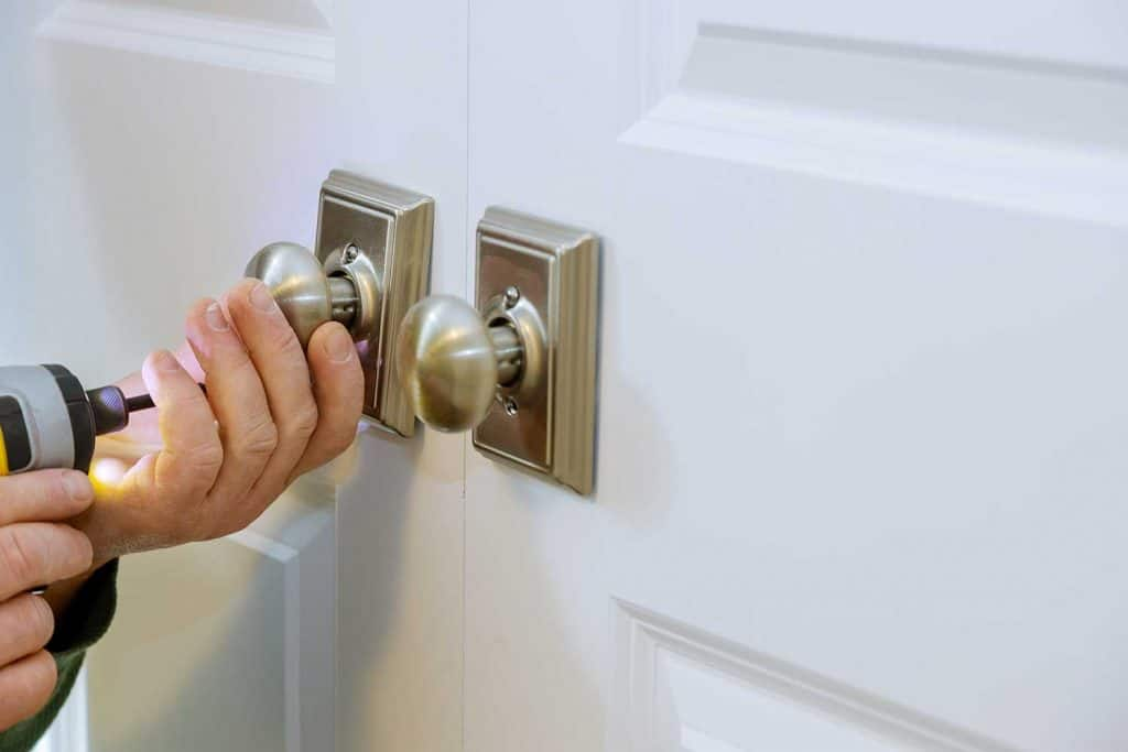 Man installing new dummy lock of the door with screwdriver