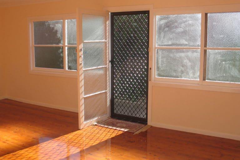 How To Keep Your Screen Door From Slamming, Sun shining through the doorway of an empty room with hardwood floorboards