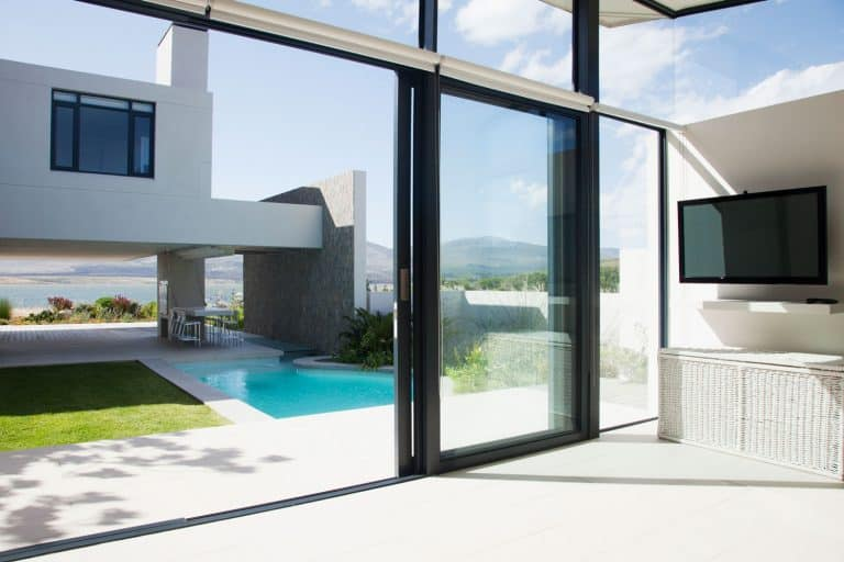 View of patio and swimming pool through sliding doors of modern house, Can A Glass Door Break from Heat?