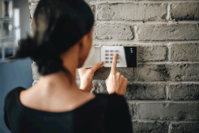 Young woman entering security pin on home alarm keypad. Home security system. How To Stop Alarm From Beeping When Door Opens