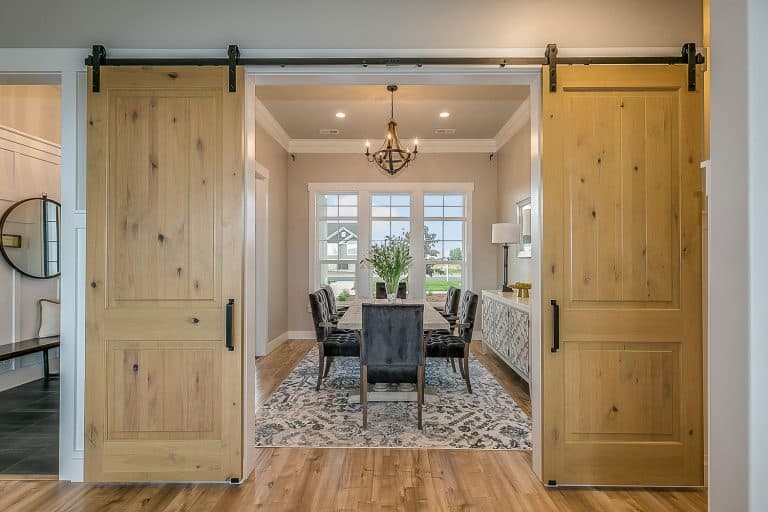 A gorgeous contemporary dining room with wooden flooring and sliding wooden barn door, Are Barn Doors Insulated?