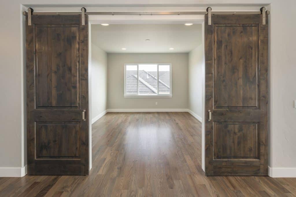 A sliding barn house door made from hard wood inside a farm style house