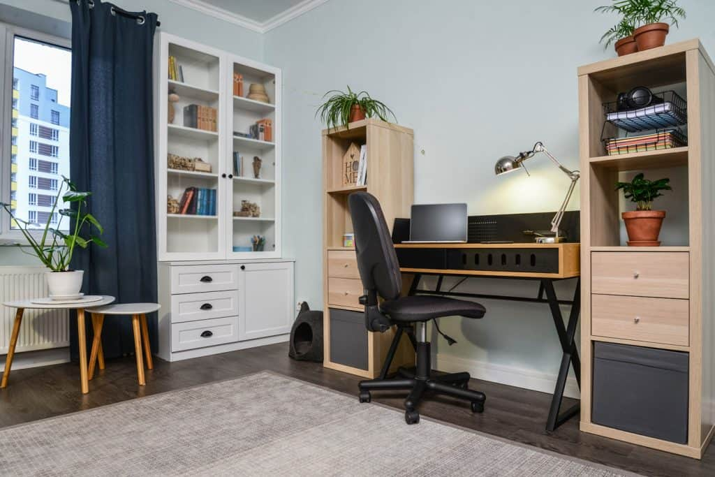 A small and cozy home office with two wooden cabinets and a gray carpet