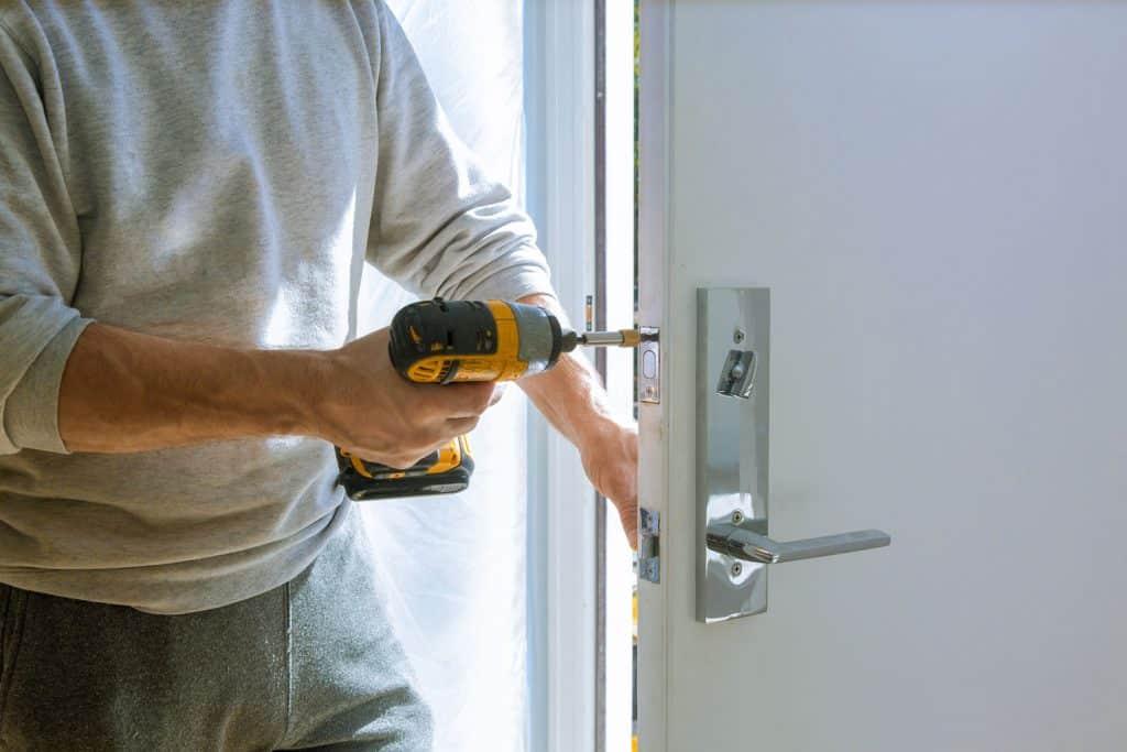 A worker adjusting the stainless steel door knob of the front door