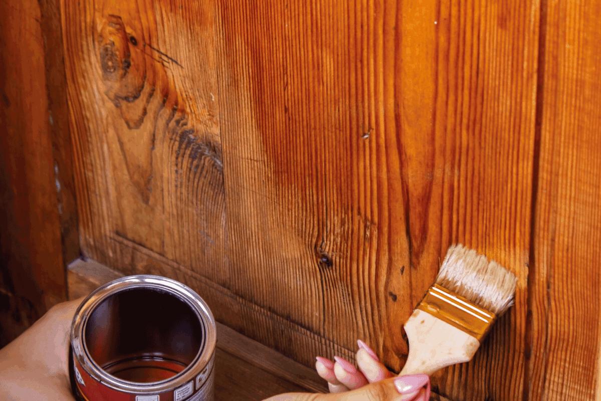 Beautiful young girl paints a wooden door. Summer work
