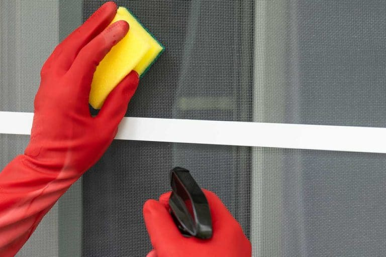 Cleaning service worker in red rubber gloves clean the mosquito net door using a spray and sponge, How To Clean A Dusty Screen Door?