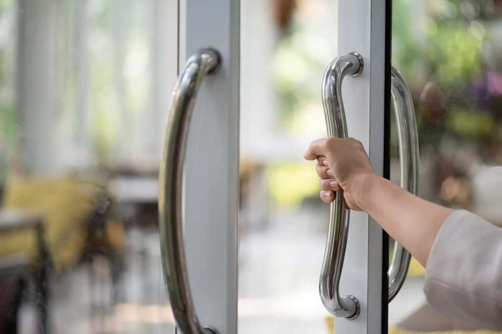 Close up of woman hand holding the door bar to open