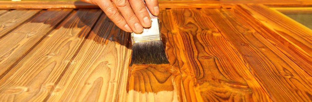 Hand of a handyman varnishing a wooden door
