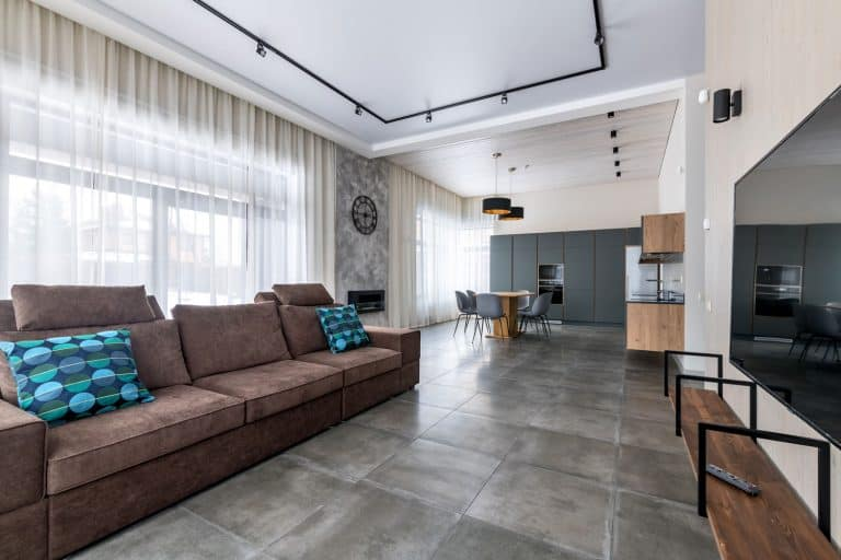 Interior of a modern and rustic inspired living room with gray flooring, gray walls, and brown rustic furnitures, What Color Doors Go With Gray Flooring?