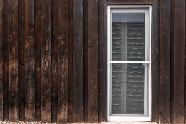 Old wooden facade of a residential building with a new fly screen door built into the patio door. Do Screen Doors Open In Or Out