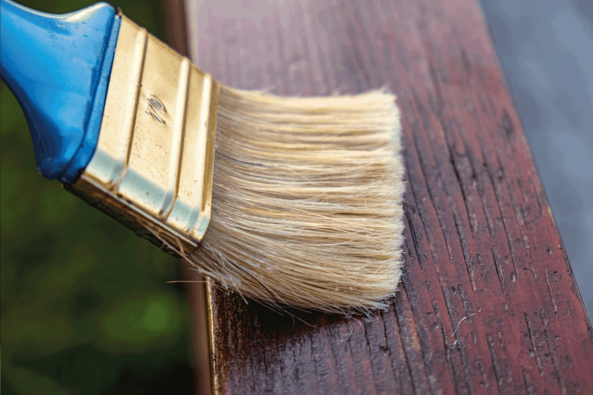 Wooden fence being painted over with wax paint by paintbrush