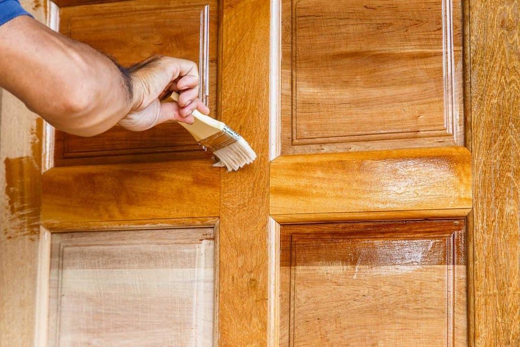 Worker hand painting wooden door with paintbrush