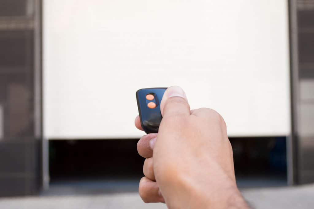 A man opening the garage door using a remote key