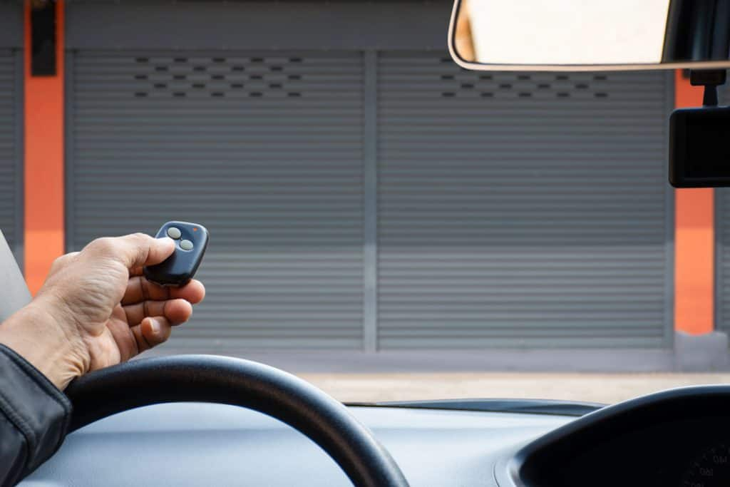 A man using his remote key to unlock the garage door
