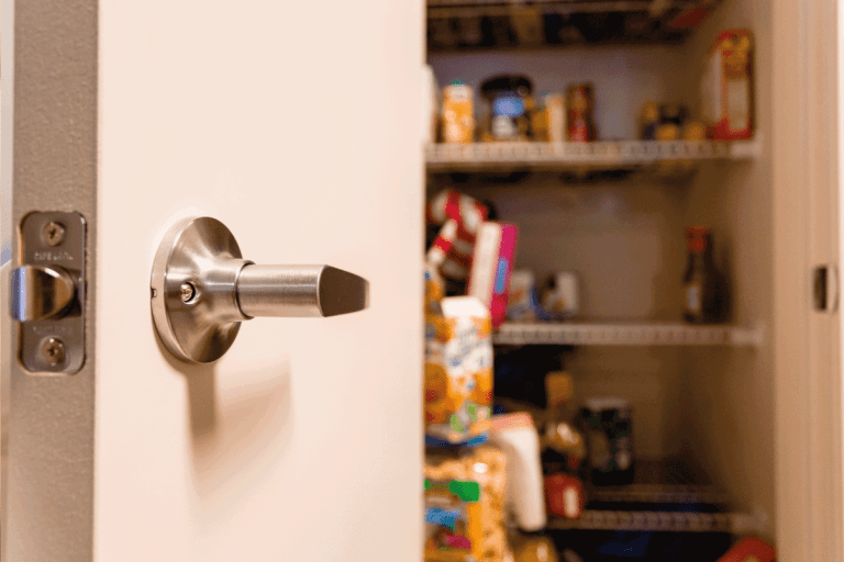 A slightly out of focus kitchen pantry is shown that is half way empty. Focus on the pantry door handle. How To Childproof A Pantry Door