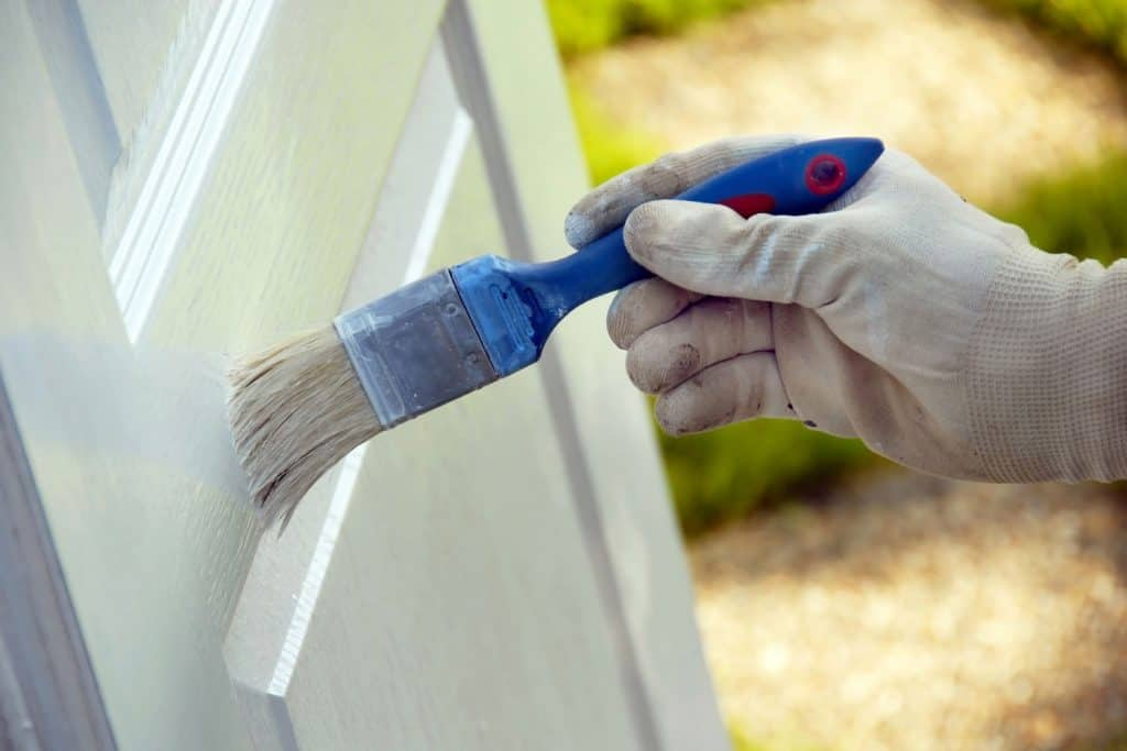 A worker painting the door with white paint