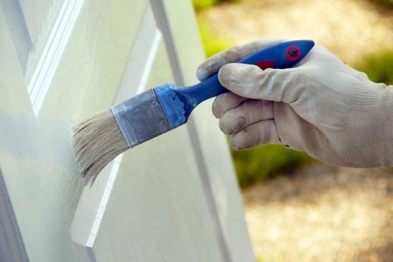 Brush in hand painting white wooden surface, How To Paint A Panel Door Without Brush Marks